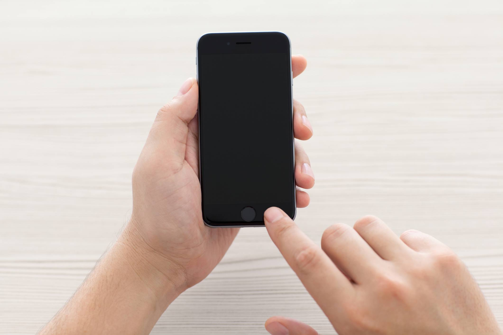 Man switch on the new iPhone 6 Space Gray holding