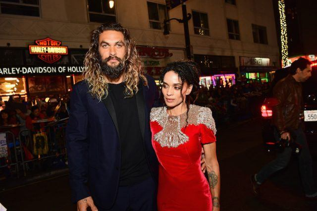 Jason Momoa and Lisa Bonet posing together as a couple on a red carpet.