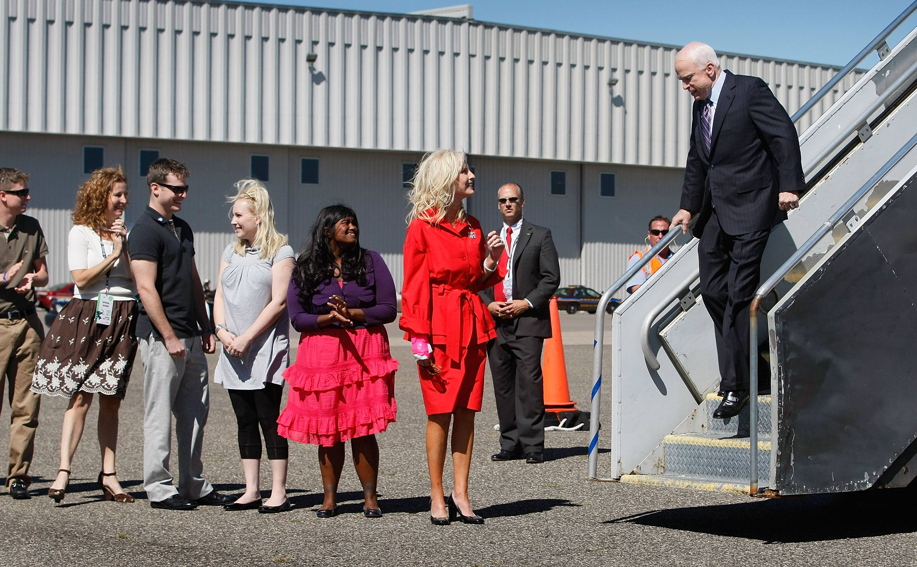 John McCain walking off plane with his family