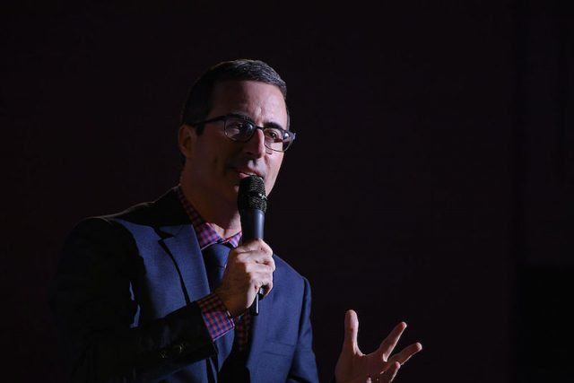 John Oliver speaking into a microphone.