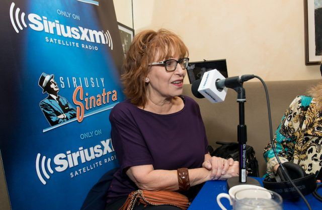 Joy Behar speaking into a large black microphone during a radio interview.