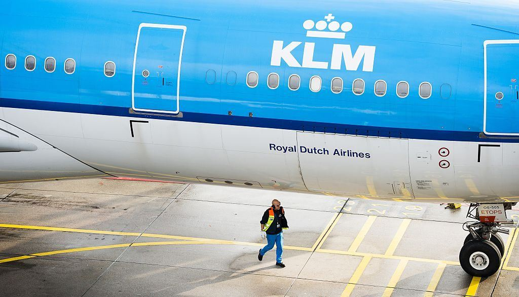 A man walks under a KLM aircraft at the Schiphol airport on October 16, 2014.