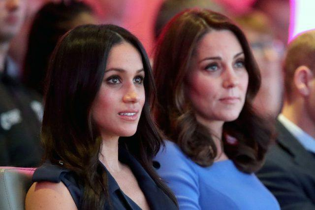 Meghan Markle and Kate Middleton sitting next to each other.