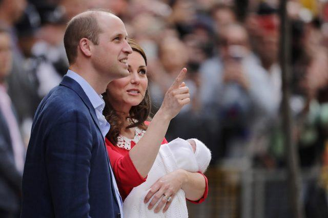 Kate Middleton pointing upwards as she holds her baby and stands next to Prince William.