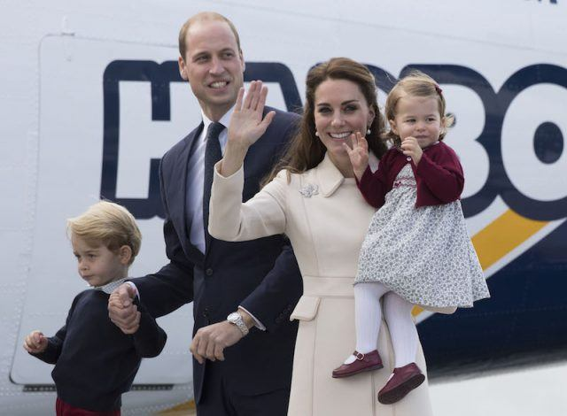 Prince William and Kate Middleton holding their two children.