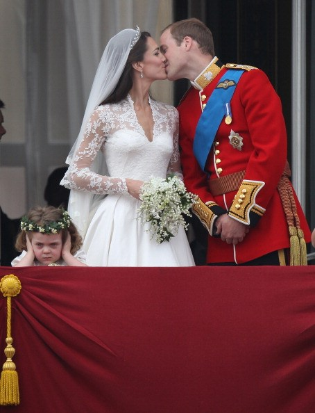 Prince William, Duke of Cambridge and Catherine, Duchess of Cambridge kiss as Bridesmaid Grace Van Cutsem (L) looks at the crowd