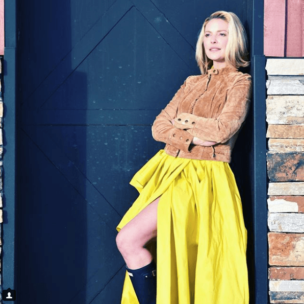 Katherine Heigl outside in a yellow skirt and brown jacket