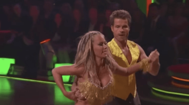 Kendra Wilkinson and Louis Van Amstel dancing in matching yellow outfits.