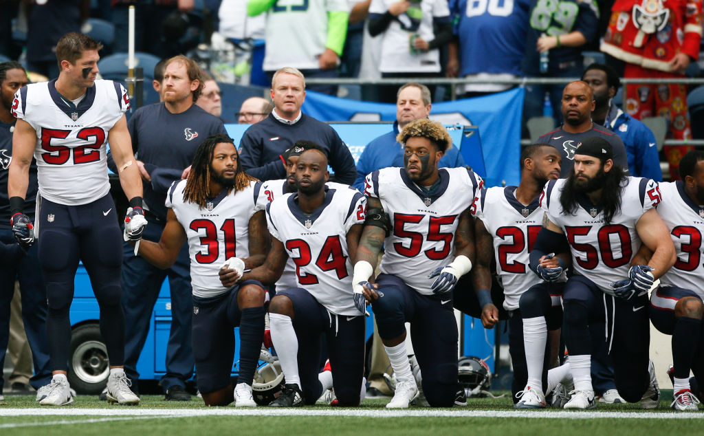 Members of the Houston Texans stand and kneel before the game