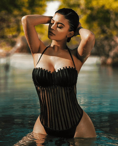 Kylie Jenner posing in a black swimsuit.