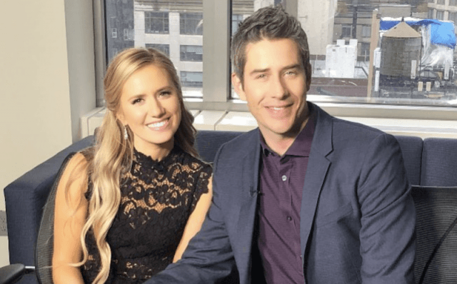 Arie Luyendyk Jr. and Lauren Burnham smiling while sitting together.