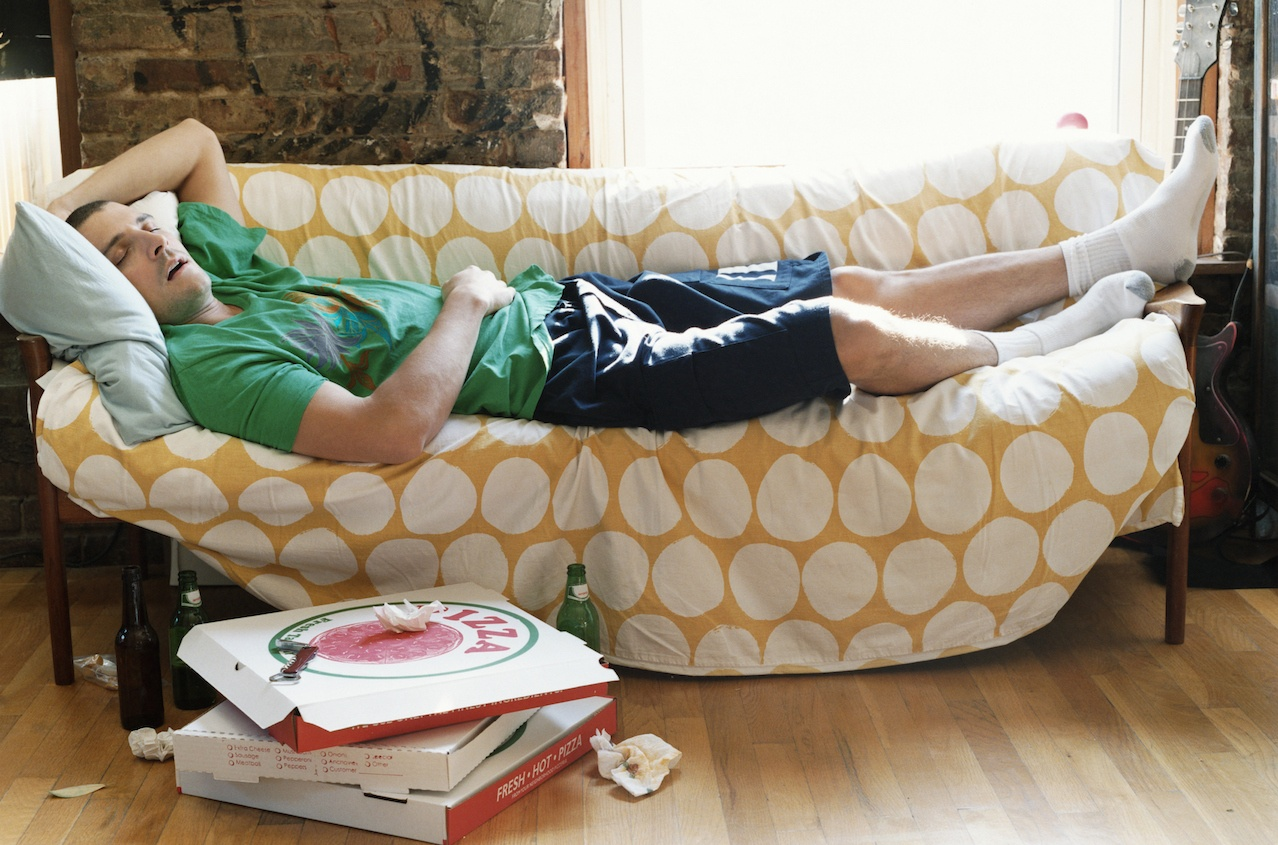 Lazy Thirty something Man Lying Asleep on a Sofa in an Apartment