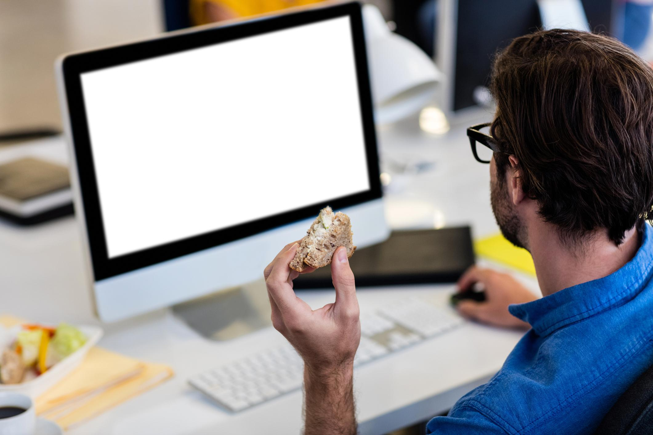 Casual businessman eating a sandwich in front of the computer