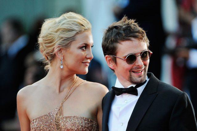 Kate Hudson and Matt Bellamy smiling at the paparazzi.
