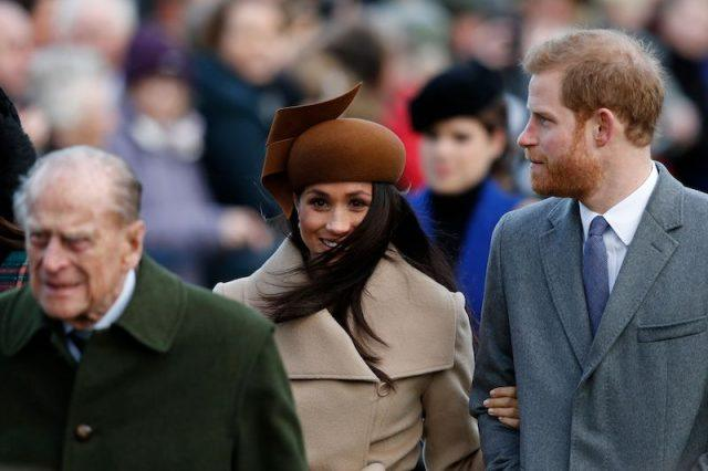 Prince Philip walking in front of Meghan Markle and Prince Harry.
