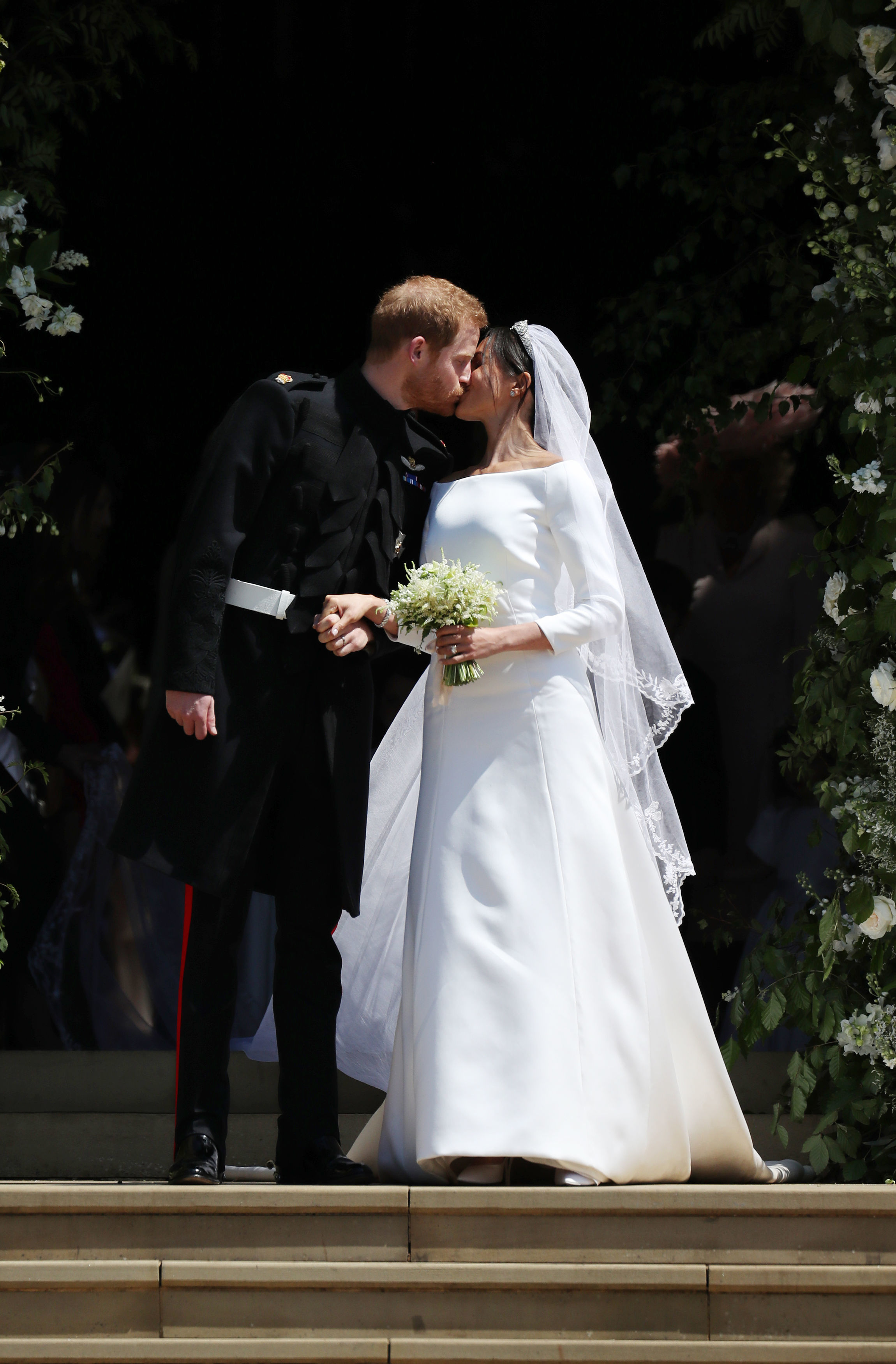 Prince Harry, Duke of Sussex and The Duchess of Sussex kiss as they leave St George's Chapel, Windsor Castle after their wedding ceremony on May 19, 2018 in Windsor, England.