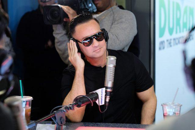 Mike Sorrentino holds his headphones during a radio interview.
