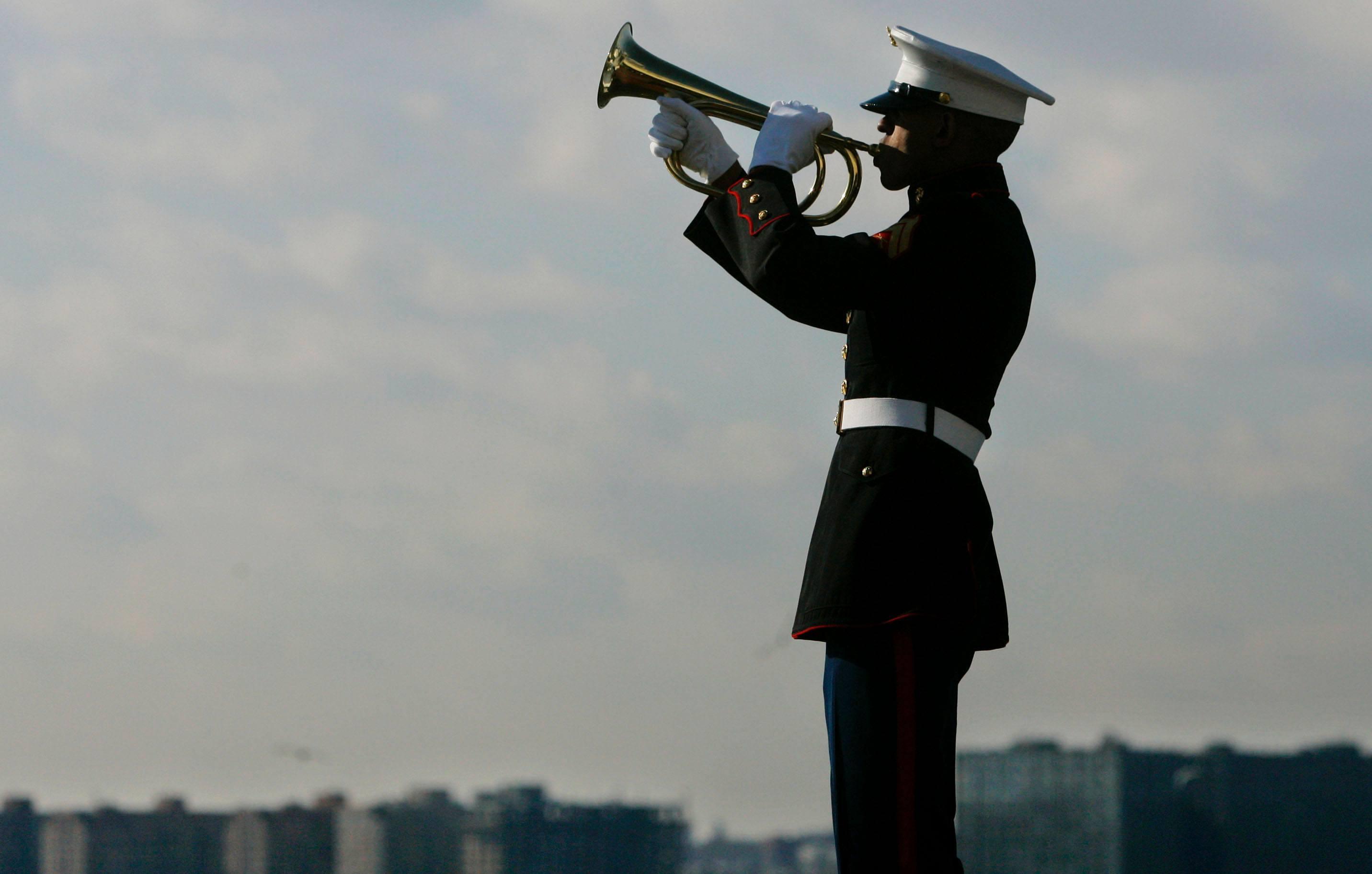 A U.S. Marine Corps bugler plays taps