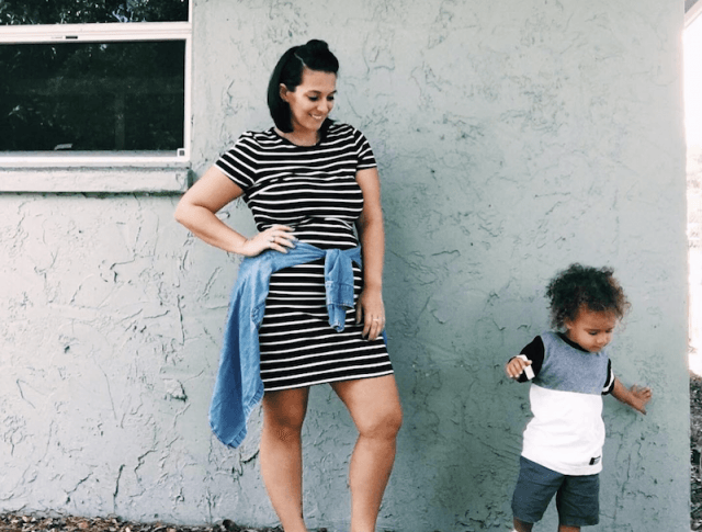 Nikki Stephens standing in front of a wall with her son.