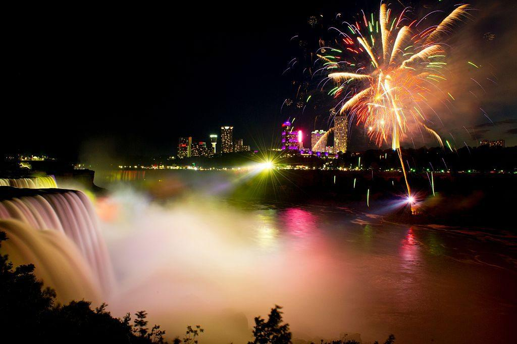 Fireworks set off from the Canadian side light up the sky over Niagra Falls late July 3, 2016, part of the July 4th US Independence Day celebrations, in Niagra Falls, New York