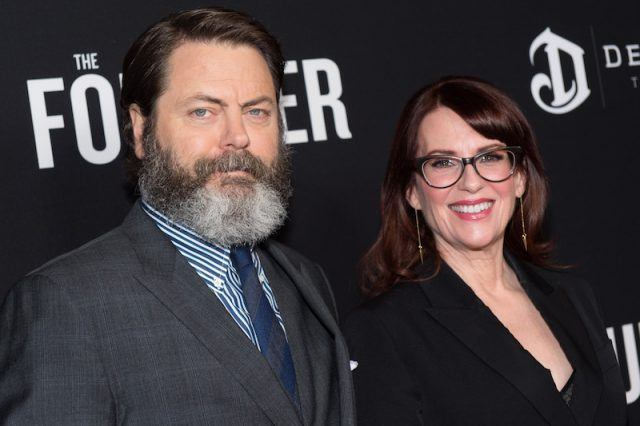 Nick Offerman and Megan Mullally posing for the paparazzi on a red carpet.