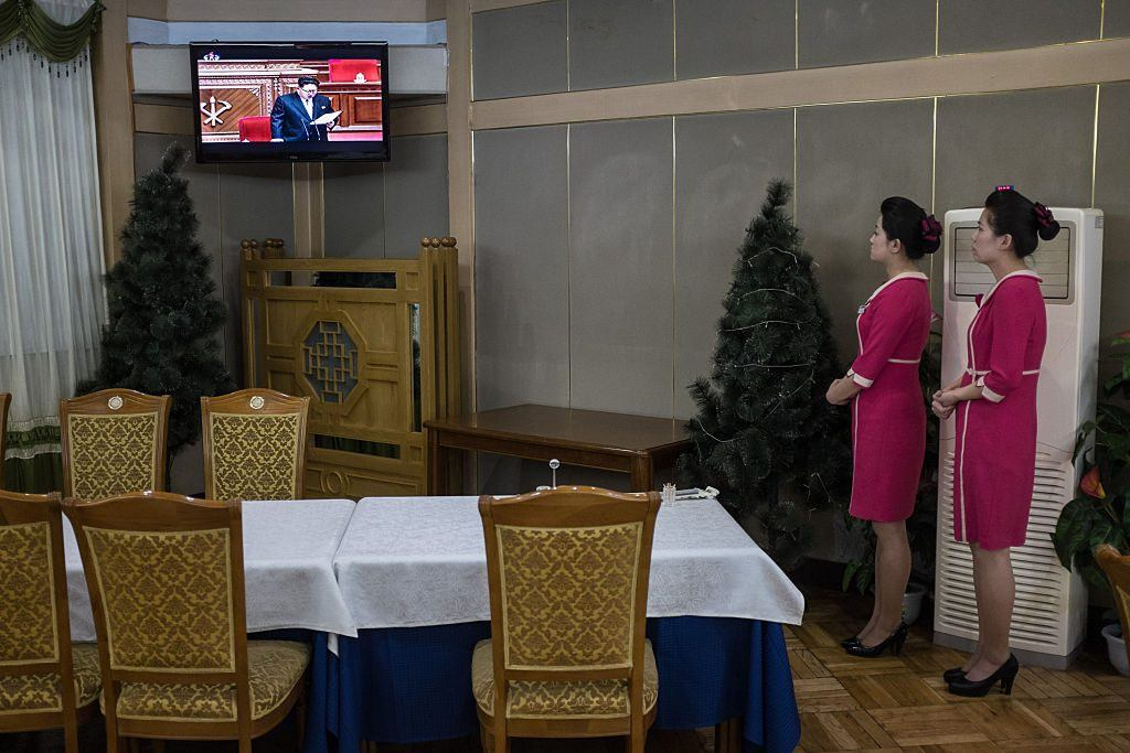 Hostesses watch a television broadcast showing a speech by North Korean leader Kim Jong Un at the 7th Workers Party Congress