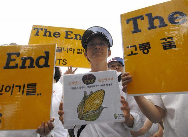 Young North Korean activists holding signs of protest against hunger and famine.