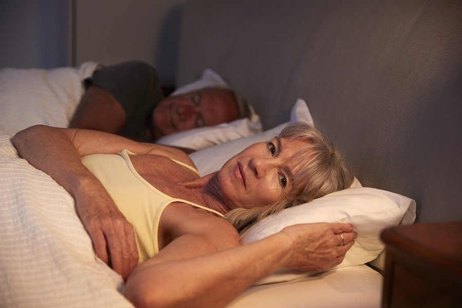 A woman in bed next to her husband
