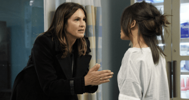 Olivia Benson bends down to speak to a young woman.