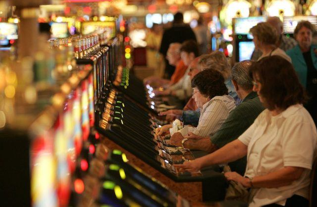 Gamblers play slot machines at the grand opening of the Beau Rivage Resort and Casino
