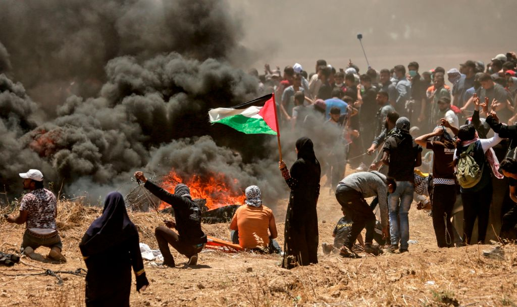 A Palestinian woman holding her national flag looks at clashes with Israeli forces