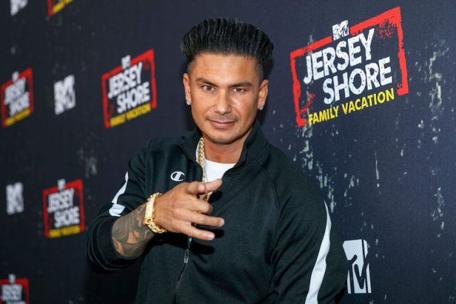 Pauly DelVecchio pointing at the camera while posing on a red carpet.