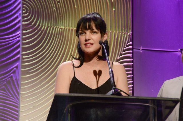 Pauley Perrette speaking into a microphone in front of a podium.