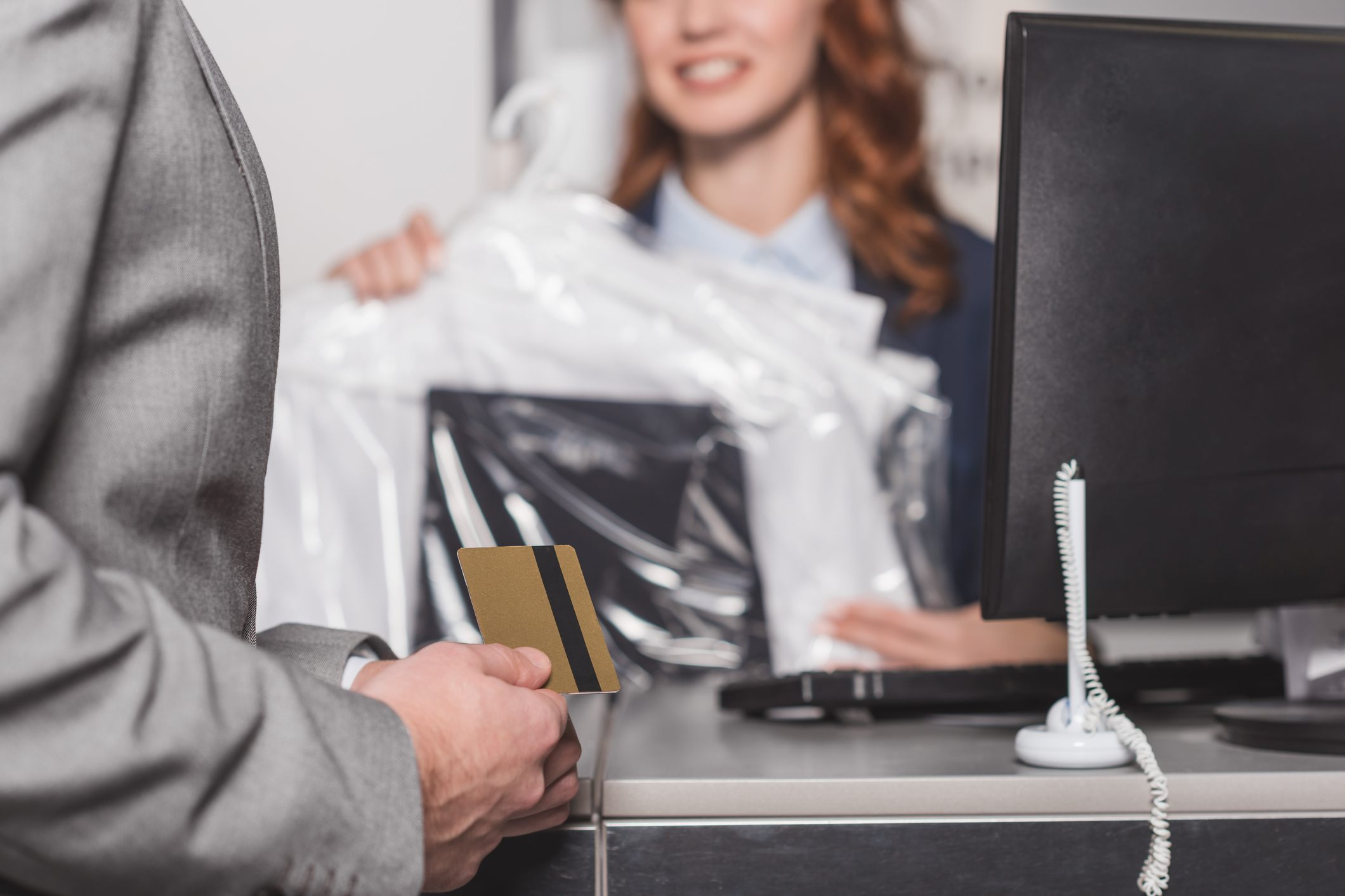 cropped shot of man holding credit card at dry cleaning office