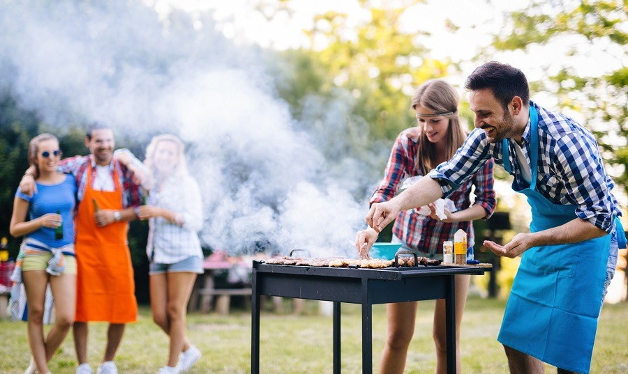 People in aprons cooking on grill