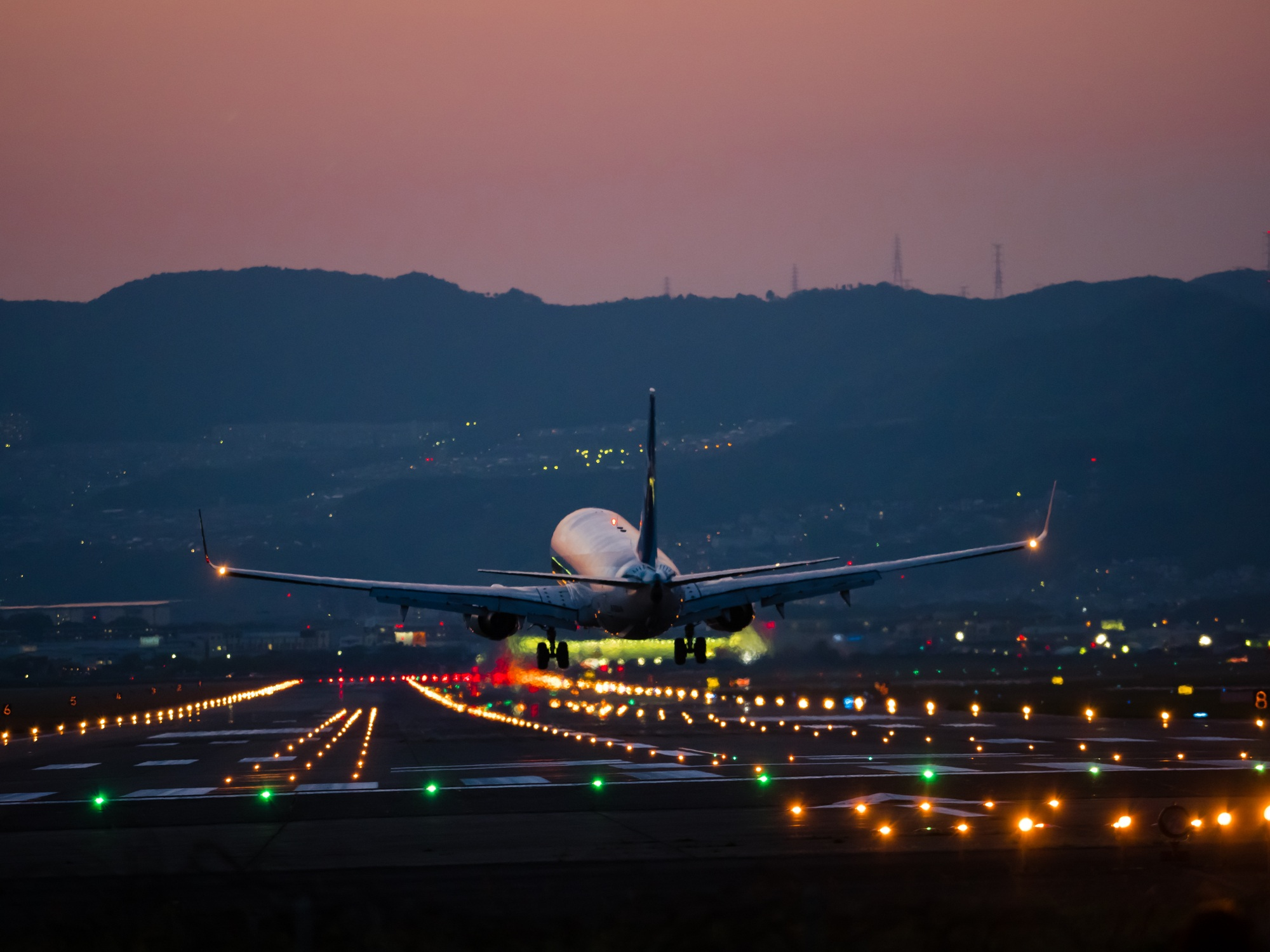 Plane landing on the runway at night with lights and a sunset