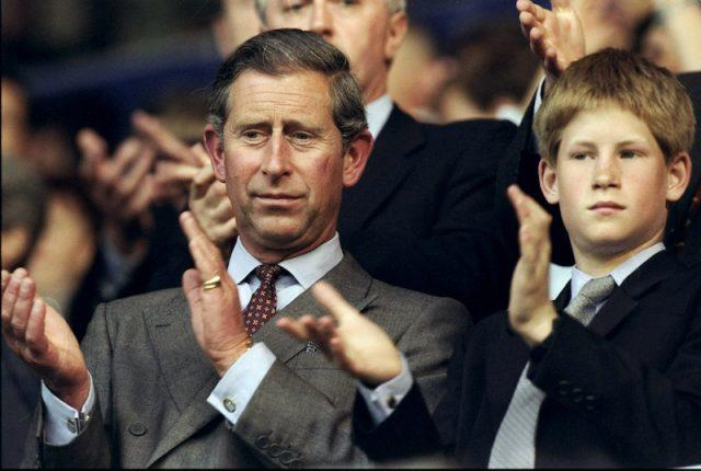 Prince Charles applauds while sitting next to Prince Harry.