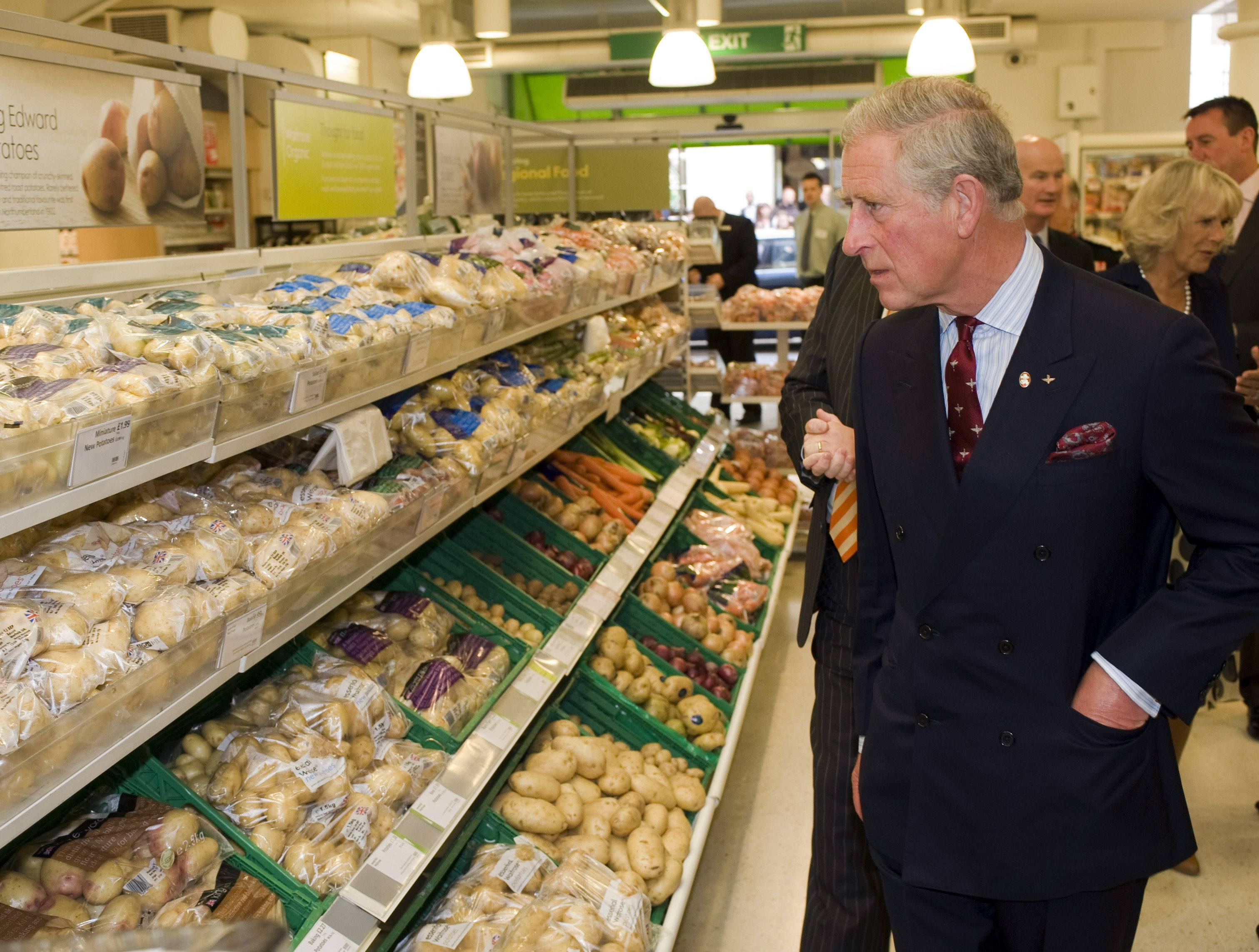 Prince Charles looking at vegetables in grocery store