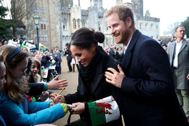 Prince Harry and his fiancee Meghan Markle sign autographs and shake hands with children as they arrive to a walkabout at Cardiff Castle.