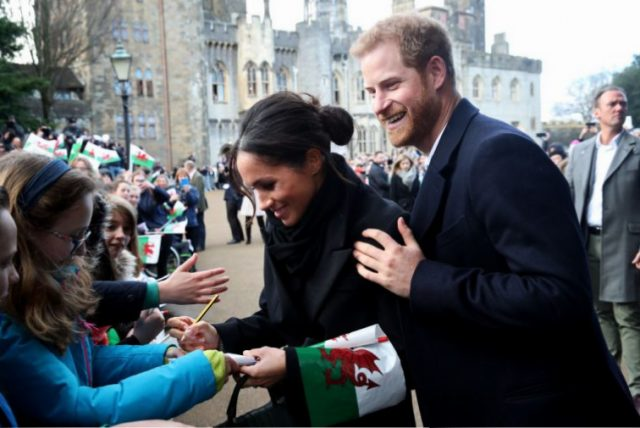 Prince Harry and his fiancee Meghan Markle sign autographs and shake hands with children as they arrive to a walkabout at Cardiff Castle