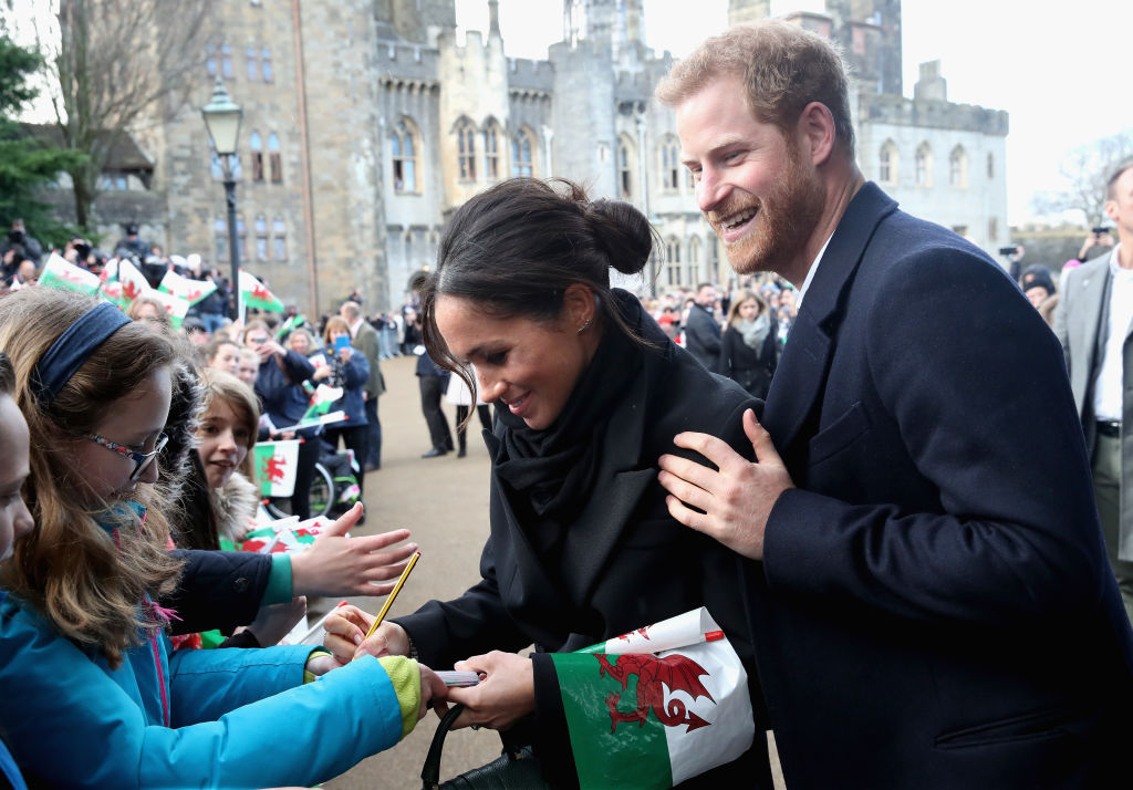 Meghan Markle writes a note for 10 year old Caitlin Clarke from Marlborough Primary School as Prince Harry looks on during a walkabout