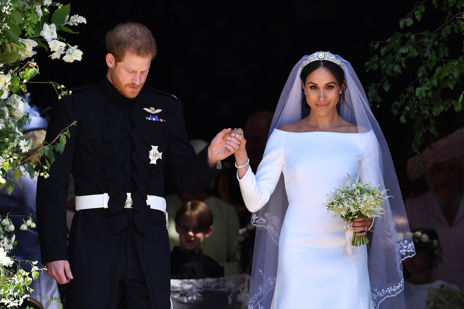 Britain's Prince Harry, Duke of Sussex and his wife Meghan, Duchess of Sussex leave from the West Door of St George's Chapel, Windsor Castle, in Windsor on May 19, 2018 in Windsor, England.