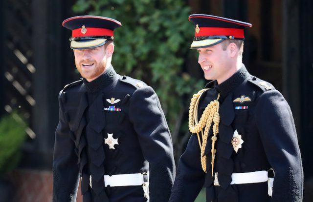 Prince Harry and Prince William walking together in their matching uniforms.