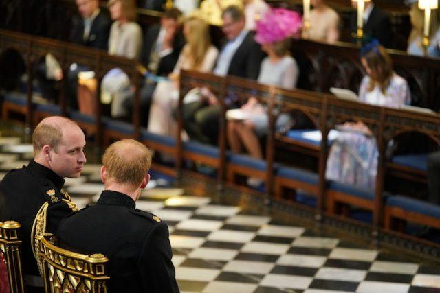 Prince William looking at Prince Harry as they sit in the church.