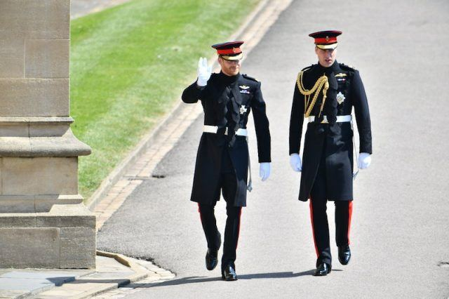 Prince Harry and Prince William walking in their matching uniforms.