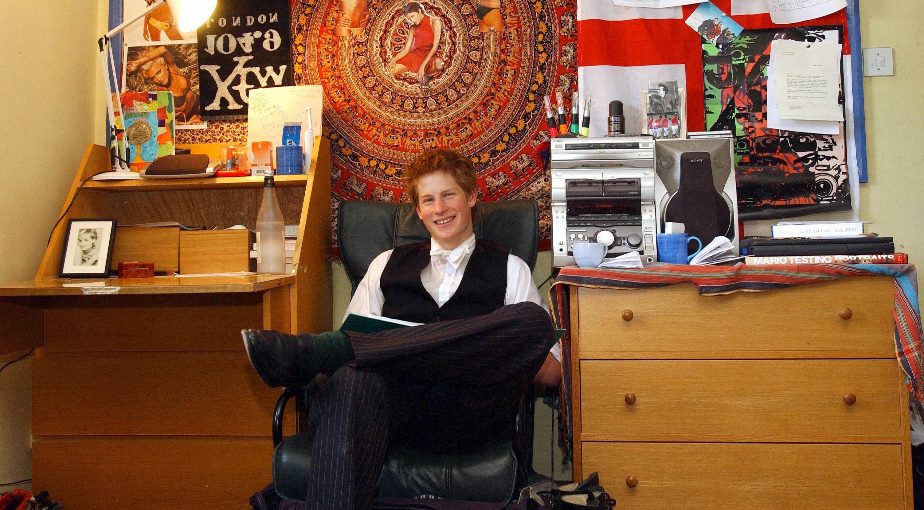 Prince Harry, the younger son of the Prince of Wales, sits 12 May 2003 in his room at Eton College. Within limits, students are allowed to decorate their room themselves.