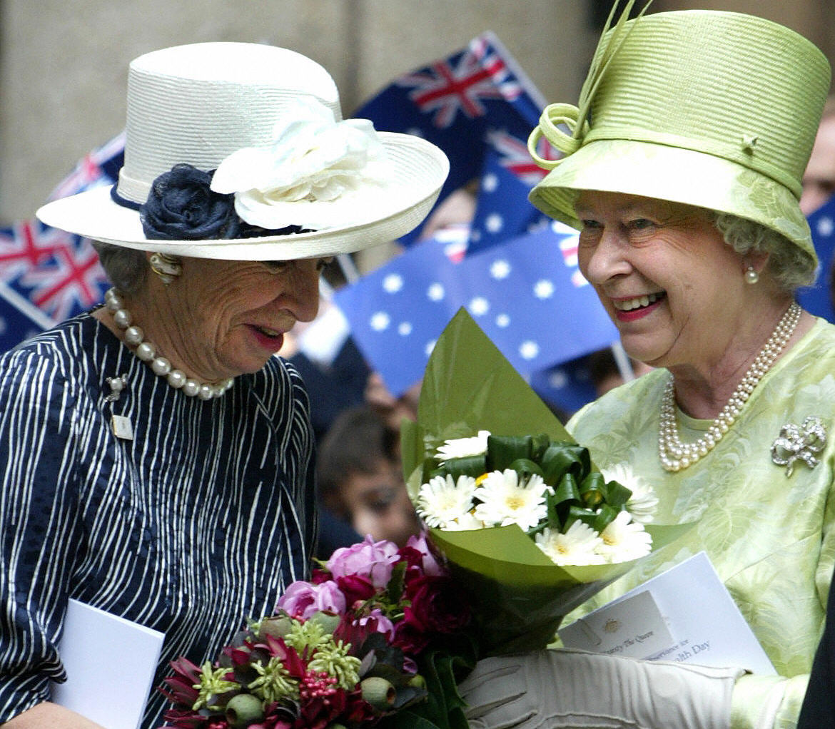 Queen Elizabeth II hands flowers to her lady in waiting