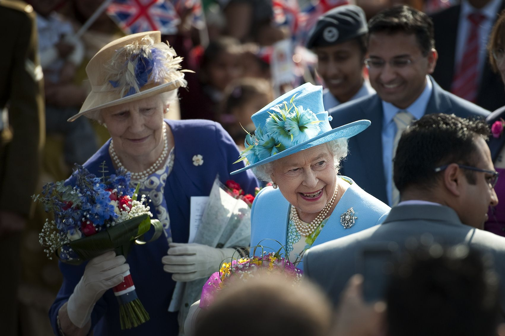 Britain's Queen Elizabeth II receives flowers from well-wishers followed by a lady-in-waiting