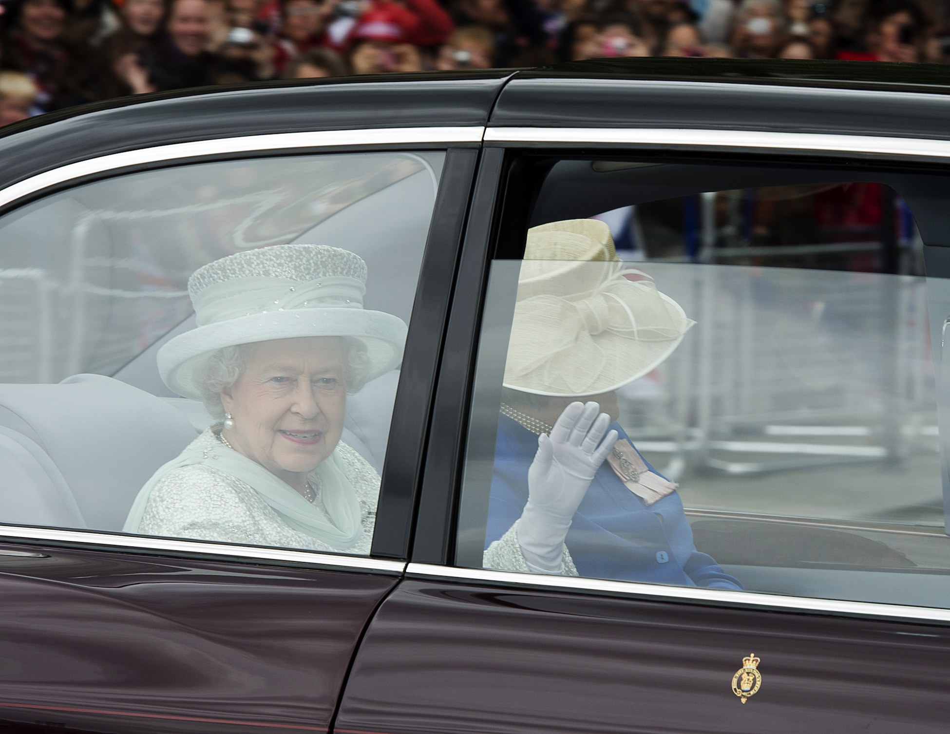 Britain's Queen Elizabeth II waves from the back of her State Limousine accompanied by a Lady in Waiting