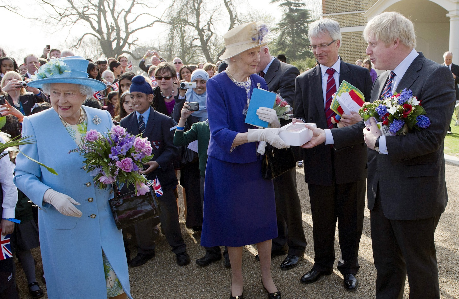 London Mayor Boris Johnson (R) and a lady-in-waiting (C) help Britain's Queen Elizabeth II (L) with her many gifts